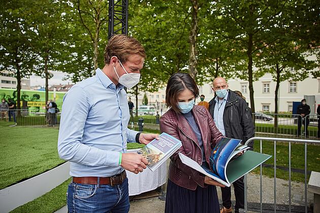 Bundestagsdirektkandidat Matthias Schwinger überreicht Annalena Baebock einen Bildband vom bayerischen Wald. - Foto: Tobias Köhler